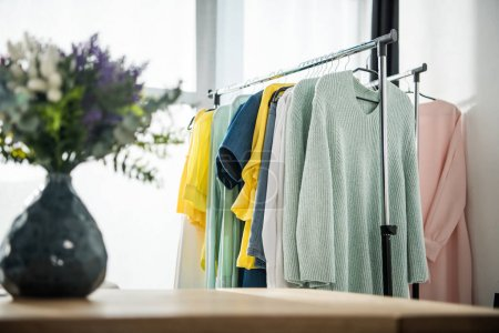 Photo for Selective focus of vase with flowers and fashionable female clothes on hangers - Royalty Free Image