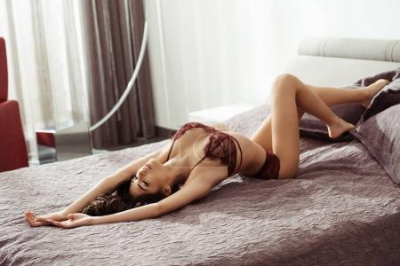 Photo for Gorgeous seductive woman in sexy lingerie lying on bed at home - Royalty Free Image