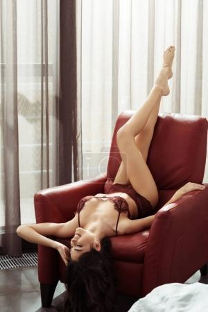 Photo for Beautiful seductive woman in sexy lingerie posing on armchair at home - Royalty Free Image