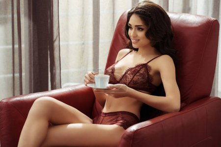 Photo for Beautiful seductive woman in sexy lingerie holding coffee cup on armchair at home - Royalty Free Image