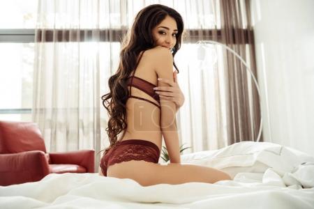 Photo pour Séduisante séduisante femme en lingerie sexy assise sur le lit - image libre de droit