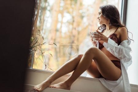 Photo for Attractive girl in lingerie and white shirt drinking coffee while sitting on windowsill in morning - Royalty Free Image