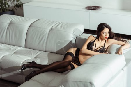 Photo for Seductive girl posing in black sexy lingerie and stockings on sofa - Royalty Free Image