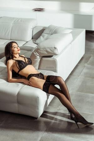 Photo for Seductive woman posing in black sexy lingerie and stockings on sofa - Royalty Free Image
