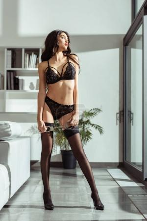 Photo for Sexy girl in black lingerie and stockings posing with handcuffs at window - Royalty Free Image