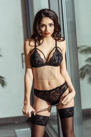 Photo pour Fille sexy en lingerie noire et bas posant avec des menottes à une fenêtre - image libre de droit