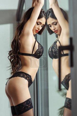 Photo pour Séduisante fille en lingerie sexy noire et bas posant à la fenêtre avec réflexion - image libre de droit