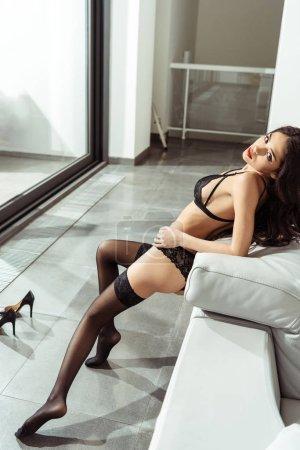 seductive woman posing on sofa