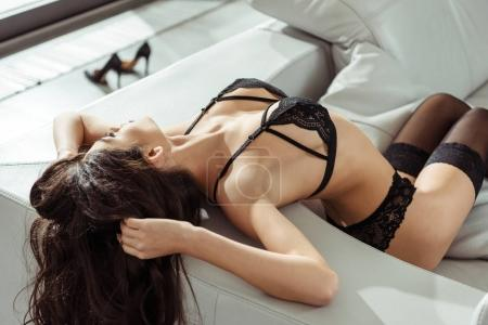 Photo for Passionate woman posing in black sexy lingerie on sofa - Royalty Free Image
