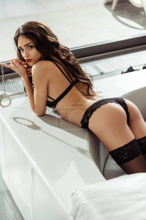 Photo for Seductive woman posing in black sexy lingerie with handcuffs on sofa - Royalty Free Image