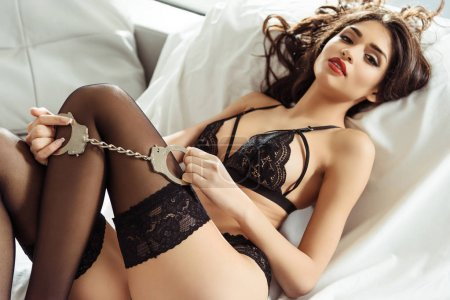 Photo for Seductive girl posing in black sexy lingerie with handcuffs on sofa - Royalty Free Image
