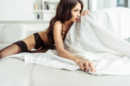 Photo for Selective focus of attractive woman posing in black sexy lingerie on sofa - Royalty Free Image