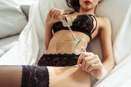 Photo pour Vue recadrée de femme séduisante posant en lingerie sexy noire avec menottes sur canapé - image libre de droit