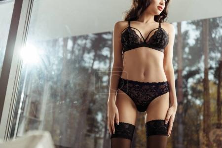 Photo pour Vue recadrée de femme sensuelle en lingerie noire avec rétro-éclairé - image libre de droit