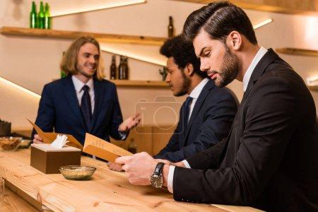 businessmen with menu in bar