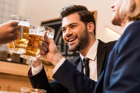businessmen clinking beer glasses