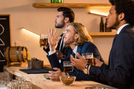 businessmen drinking beer and watching match