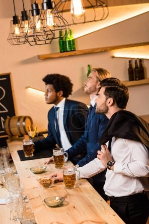 businessmen drinking beer in bar