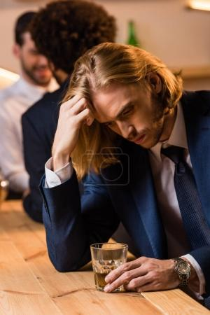 Photo for Depressed young businessman drinking whisky in bar - Royalty Free Image