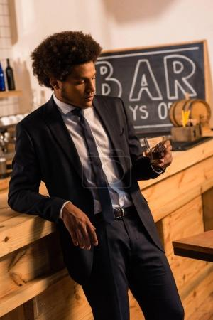 Photo for Drunk african american businessman holding glass of whisky in bar - Royalty Free Image