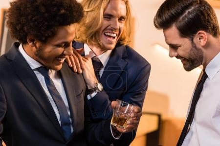 Photo for Three multiethnic businessmen laughing while drinking whiskey in bar - Royalty Free Image