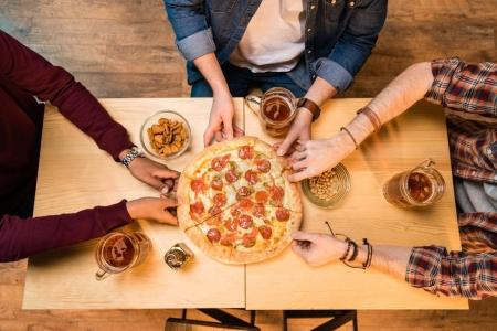 men drinking beer and eating pizza