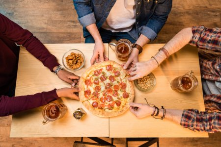 Photo for Top view of young men drinking beer and eating pizza - Royalty Free Image