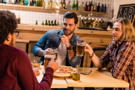 friends with pizza and beer in bar