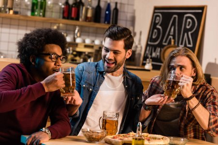 Photo for Young friends drinking beer and having fun together in bar - Royalty Free Image