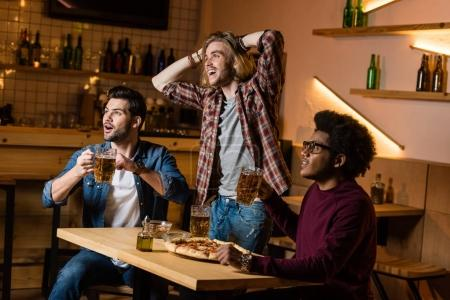 friends with beer watching match in bar