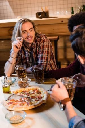 Photo pour Plan recadré de jeunes hommes se regardant tout en mangeant de la pizza et en buvant de la bière dans un bar - image libre de droit