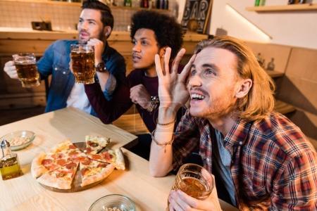 Photo pour Émotionnel jeunes hommes multiethniques boire de la bière et manger de la pizza tout en regardant le match de football dans le bar - image libre de droit