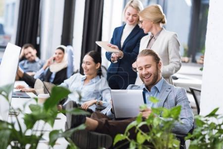 Photo pour Mise au point sélective des jeunes souriant des gens d'affaires sur les lieux de travail au bureau - image libre de droit
