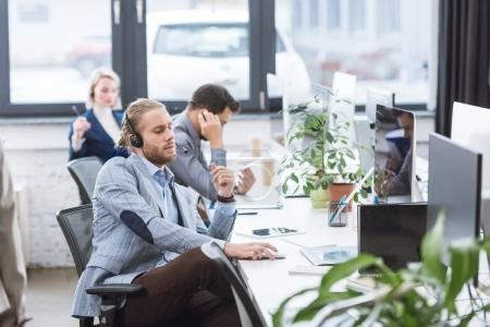 Photo for Selective focus of call center operator in headset sitting at workplace in office - Royalty Free Image