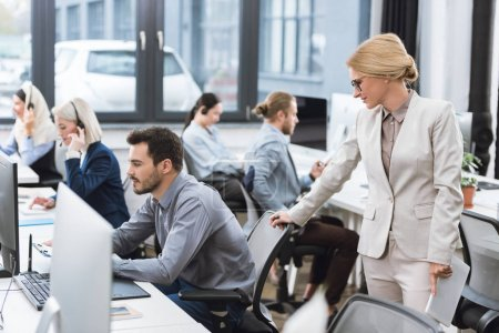 Photo for Selective focus of businesswoman looking at colleague working in office - Royalty Free Image