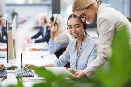 Foto de Enfoque selectivo de sonriente multiculturales empresarias usando tableta juntos en el lugar de trabajo en oficina - Imagen libre de derechos