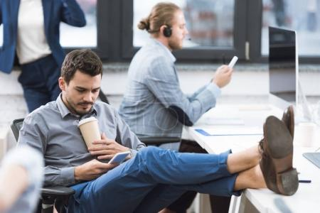 businessman with coffee to go and smartphone in office