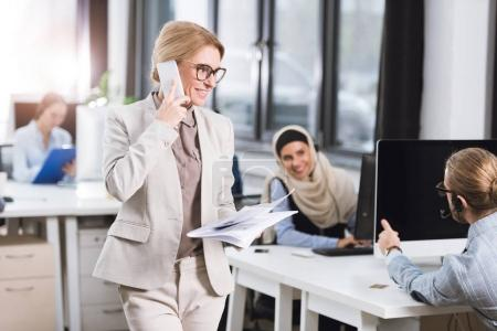 businesswoman with newspaper talking on smartphone
