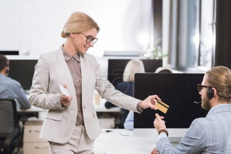 businesswoman giving credit card to colleague