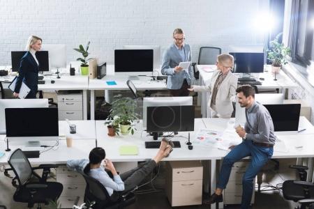 Photo pour Vue d'angle élevé de collègues de travail au bureau - image libre de droit