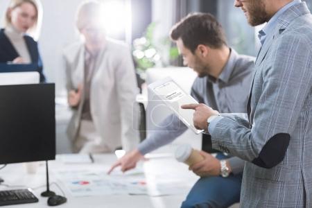 Foto de Enfoque selectivo del empresario uso tableta durante el trabajo en la oficina - Imagen libre de derechos