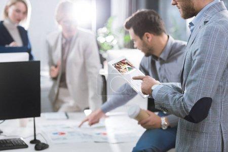 Foto de Enfoque selectivo del empresario con tablet in logo en pantalla durante el trabajo en la oficina - Imagen libre de derechos