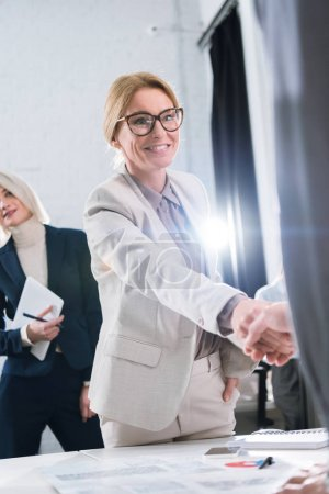 businesswoman and colleague shaking hands