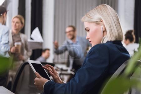 Foto de Enfoque selectivo de la empresaria enfocada en auriculares utilizando tableta en la oficina - Imagen libre de derechos
