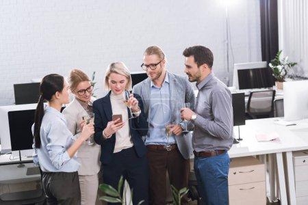 Photo pour Équipe de jeunes entrepreneurs boire le champagne ensemble après le travail au bureau - image libre de droit
