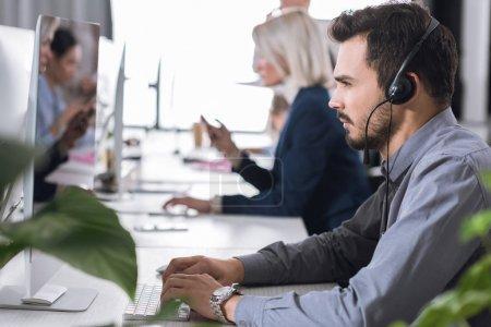 Photo pour Mise au point sélective d'opérateur de centre d'appel ciblé dans l'oreillette au bureau - image libre de droit
