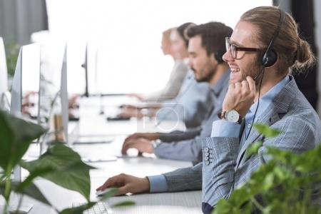 Photo pour Mise au point sélective d'opérateur de centre d'appel joyeux dans l'oreillette au bureau - image libre de droit