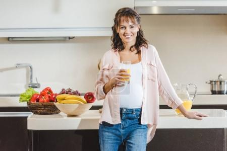 Photo for Happy young pregnant woman with juice in glass looking at camera at kitchen - Royalty Free Image