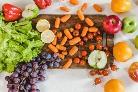 Photo for Top view of table with fruits and vegetables on chopping board at kitchen - Royalty Free Image