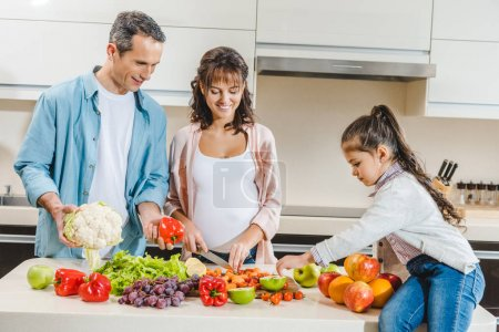 Photo for Cheerful family with pregnant mother slicing vegetables and fruits at kitchen - Royalty Free Image